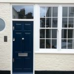 Panelled front door with sash windows